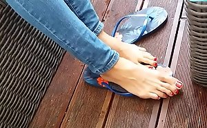 Dispirited teen with pounding toes showing her feet at the shore